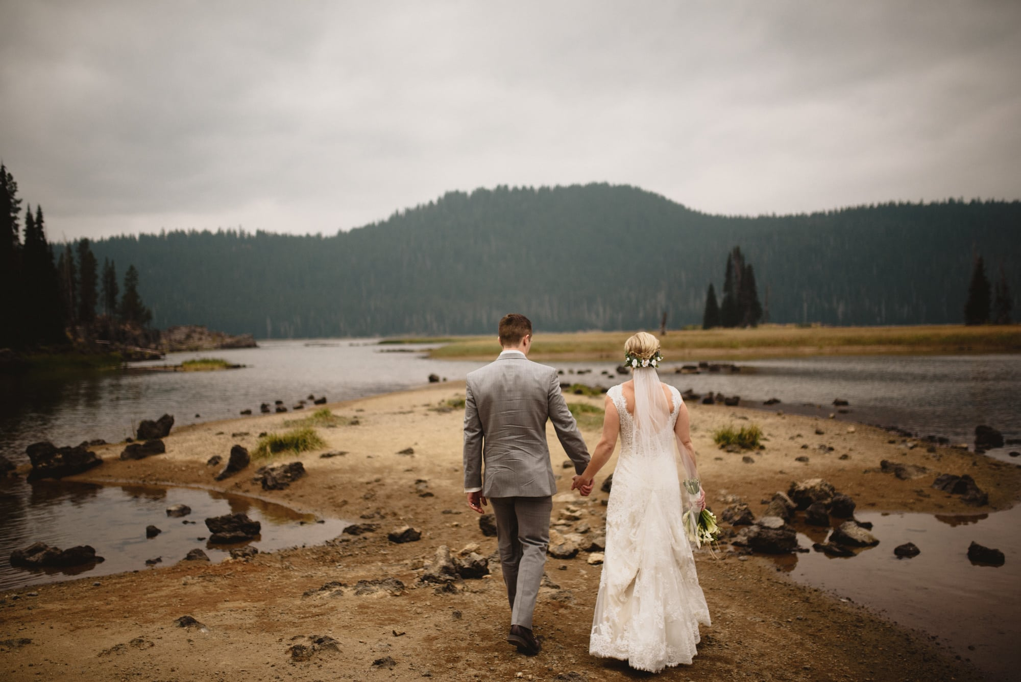 Carly and Danny are from Baltimore, MD and chose Bend, Oregon for their Elopement. After a little internet research decided on a Sparks Lake for their ceremony. Neither of them had ever been to Oregon, so they were up for an adventure. In the week leading up to their ceremony date several fires had started to break out through Oregon. There were three fires specifically that surrounded Sparks Lake. For several days, you could not see across the lake, and it was highly recommended not to breath the air. I scouted Sparks Lake with Carly and Danny the day before their wedding and the smoke was so intense we could stare straight at the sun. After a short conversation, they both decided that since they had already traveled across the country, they would embrace the elements. Within a day the weather changed. On our way up to the mountain a thunderstorm blew in. Thunder, lighting, and rain started right along with their ceremony. By the end of their ceremony, performed by Wendy Duncan, they skies cleared and the sun popped out. It was magical, to say the least. After their ceremony they shared a toast and we started taking portraits. Every where we turned the light was changing and the backdrops became more amazing. We headed out on the lake and were quickly surrounded by a stunning smokey/stormy sunset. Every direction we shot was amazing. I'm so glad that Carly and Danny stayed optimistic about all the smoke and didn't let them spoil their wedding. Also a big shout out to Summer Robbins for the beautiful bouquet and Cassidy Elise for Carly's hair and makeup. I definitely want to shoot more of these adventurous outdoor elopements. So if you're thinking about eloping email or call me asap.